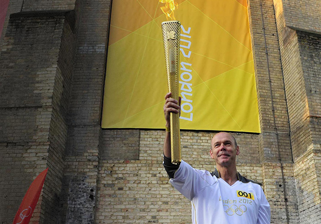 Clive holding the olympic torch in the air.